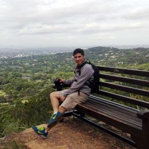 En man sitter på en stor bänk uppe på ett berg. I bakgrunden syns gröna träd och en stad.