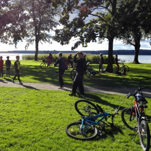 En park där det går och cyklar flera barn som spelar Pokémon Go.
