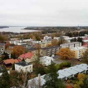 Vy över Ekenäs centrum tagen uppifrån. På bilden syns hustaken av flera höghus och till vänster i bild syns Pojoviken.