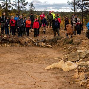 ihmisiä kaivupaikkaa katsomassa hiekkamaassa