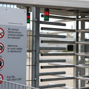 Kuvassa näkyy kielto- ja varoitusmerkkejä sekä kulkuportti tehdasalueelle.