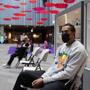 En ung man med munskydd sitter i köpcentermiljö. Han har vaccinerats, och väntar på att få gå.