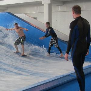 Två personer surfar i en inomhus surfbassäng medan en tittar på.