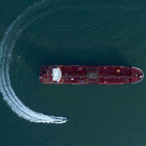 En båt åker runt ett tankerfartyg.