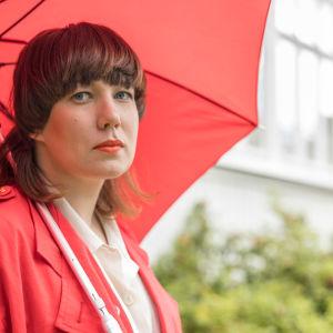Litku Klemetti ulkona punaisen sateenvarjon alla