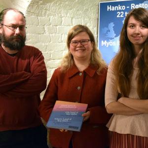 Tre människor upp en bok.