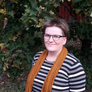 Kirjailija Anne Leinonen syksyisen puun edessä