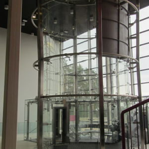 En vindtunnel invid ett stort fönster. Vindtunneln ser ut som en gigantisk cylinder av glas.