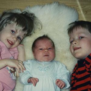 Kolme pientä lasta; tyttö, vauva ja poika makaavat lampaantaljalla selällään ja katsovat kameraan hymyillen.
