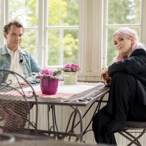 Juha Itkonen ja Ellinoora istuvat puutalon terassilla.