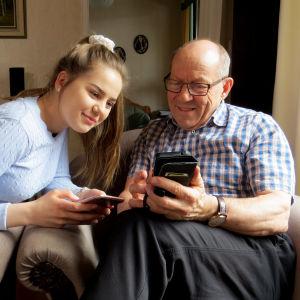 Lastenlapsi opettaa vaarille Twitteriä puhelimella.