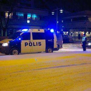 Polisbil står med blåljusen på i centrum av Pargas, polis står bredvid polisbilen och dirigerar trafiken.
