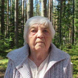 En äldre dam tittar rakt in i kameran. Bakom henne tät skog.