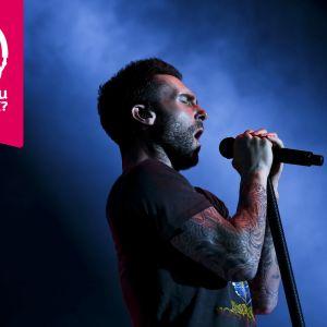 Adam Levine sjunger i en mikrofon som han håller om med bägge händer.