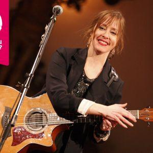 Suzanne Vega ler med en akustisk gitarr i famnen.