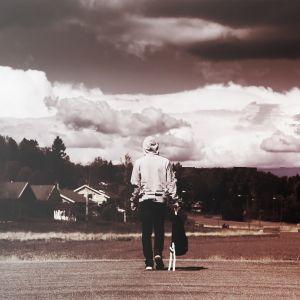 Ung människa vandrar bort över en bro.