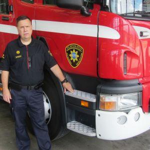 Räddningschef Peter Johansson vid en släckningsbil av samma typ som den som ska bytas ut