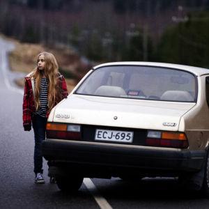 Tolvåriga Varpu står ensam på en landsväg utanför en övergiven bil.