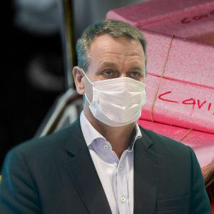 """Bildmontage av tre bilder. I bakgrunden syns rosa lådor med texten """"covid"""" på. Till vänster syns en bild av Helsingfors borgmästare Jan Vapaavuori, till höger en bild av statsminister Sanna Marin. Båda bär munskydd."""