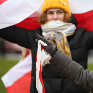 Old woman with an unofficial flag of belarus