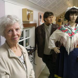 Dorrit Krook Igor-museossa kansallispukuisen mallinuken vieressä.