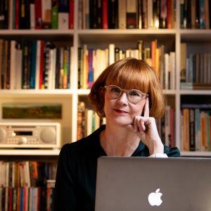 Suna Vuori istuu kirjahyllyn edessä tietokoneensa ääressä.