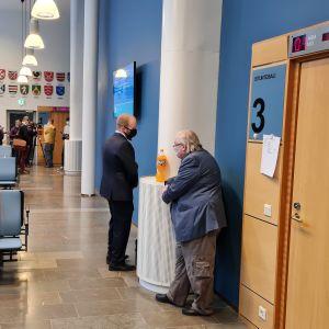 Målsägande Pekka Kataja (till höger) i tingsrättens korridor.
