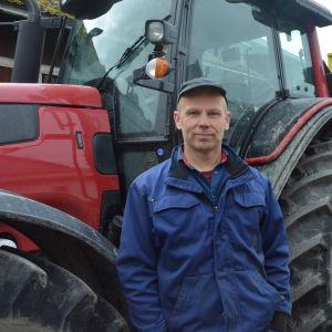 En man, bonde, står framför sin traktor.