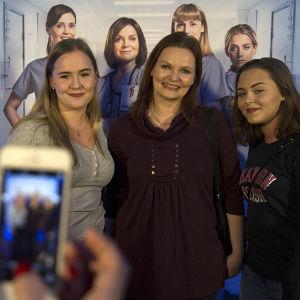 Krista Putkonen-Örn poseeraa kahden fanin kanssa Syke-fanitilaisuudessa.
