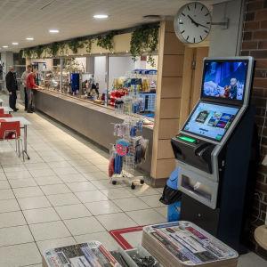 Ihmisiä Oulun uimahallin kahvilassa, Veikkauksen peliautomaatti kahvilan lähellä