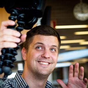 Ville mäkipelto pitää kameraa kädessään, katsoo kameraan ja hymyilee