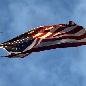 Amerikansk flagga på hög stång med örnprydnad i guld.
