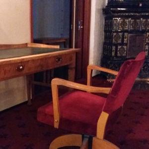 Ett gammalt skrivbord och en röd skrivbordsstol.