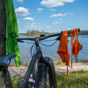 Läskipyörä kansallispuistossa järvenrannalla. Uima-asu kuivuu ohjaustangolla.