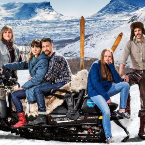 Huvudkaraktärerna i Andra åket vid en snöskoter med fjäll i bakgrunden.