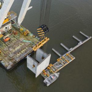 Stora betongelement sätts på plats i hamnbassängen i Vasa hamn med hjälp av en specialkran som står på en ponton.