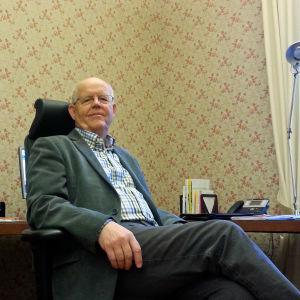 Gustav Björkstrand sitter i kontorsmiljö och tittar avslappnat in i kameran.