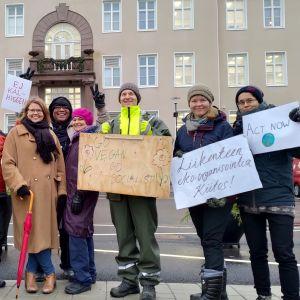 Demonstranter med plakat står utanför stadshuset i Raseborg.