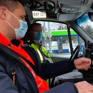 Två män med munskydd sitter i en ambulans och tittar på en skärm.