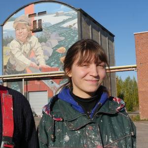Taiteilijat Taneli Stenberg ja Anetta Lukjanova muraalin edustalla Kuusankoskella Kymin Ruukin alueellae