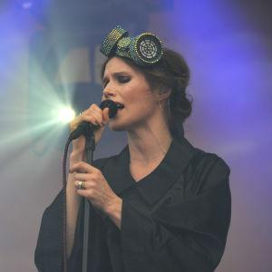 Sångaren Nina Persson uppträder på en lilafärgad scen på Rusrock.