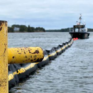Öljyntorjunta-alus ja puomit vedessä. Harjoitus Kotkassa.