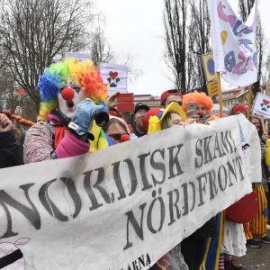 """Motdemonstranter utklädda till clowner håller stor banderoll där det står """"Nordisk skam! Nördfront"""""""