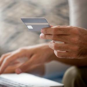 Hand som håller i ett kreditkort medan den andra handen knackar på ett tangentbord till en bärbar dator.