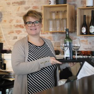 Maija Munkki tarjoilee viiniä.