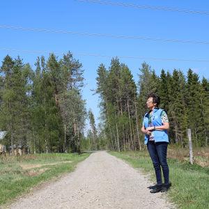 Helena Kreivi katselee voimalinjaa talonsa läheisyydessä Ylitorniolla.