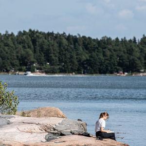 Ihmiset nauttivat ulkona Haukulahden uimarannalla.