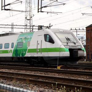 Ett grönvitt Pendolino-tåg på en bangård.