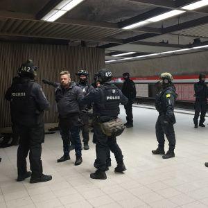 Tungt utrustade poliser har stoppat personer på metroperrongen.