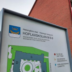 Skylt utanför en tegelbyggnaden där det står Hoplaxskolan.